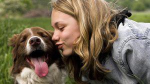 Mulher beijando cachorro